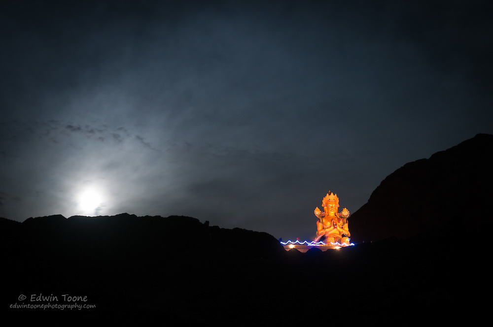 A 60 foot tall Buddha stands in the Nubra Valley as the moon rises.