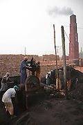 Factory workers operate machinery at the JRB brick factory near Sonargaon, outside Dhaka, Bangladesh. The heavy clay soils along the river near the market town of Sonargaon are well suited for making bricks. At the JRB brick factory, workers of all ages move raw bricks from long, stacked rows, where they first dry in the sun, to the smoky coal-fired kilns. After being fired, the bricks turn red. A foreman keeps tally, handing the workers colored plastic tokens corresponding to the number of bricks they carry past him. They cash in the chips at the end of each shift, taking home the equivalent of $2 to $4 (USD) a day.
