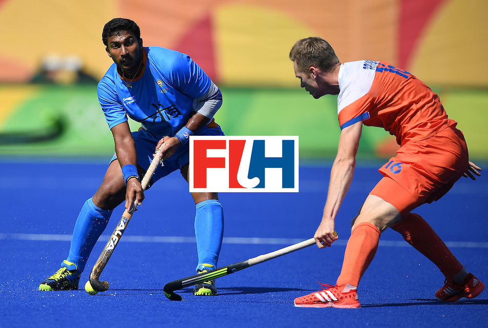India's Raghunath Vokkaliga (L) looks to pass as Netherland's Mirco Pruijser tries to stop him during the men's field hockey Netherland's vs India match of the Rio 2016 Olympics Games at the Olympic Hockey Centre in Rio de Janeiro on August, 11 2016. / AFP / MANAN VATSYAYANA        (Photo credit should read MANAN VATSYAYANA/AFP/Getty Images)