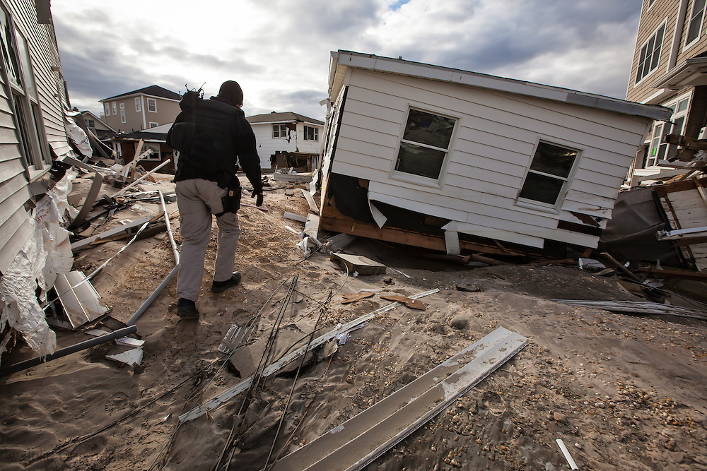 Police officer walks in the ruins of Ortley Beach New Jersey a few days after Hurricane Sandy hit the coast.