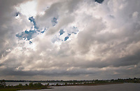 crossing the Blackwater River on interstate 10 in Florida with a cloud-filled sky.