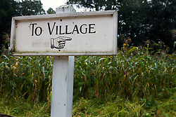 "A sign with a hand pointing to the right reading ""To Village"", Old Sturbridge Village (OSV), a re-created New England town of the 1830s, is a living history museum in Sturbridge, Massachusetts.  OSV, the largest living museum in New England, stands on 200 acres on farm land that once belonged to David Wight."
