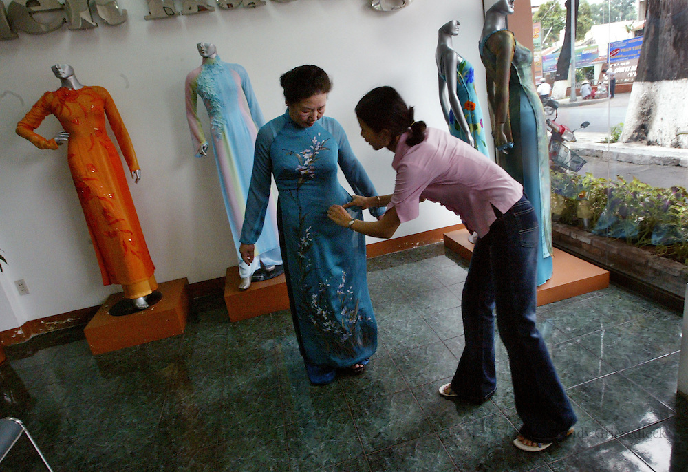 Mai Nguyen tries on a dress at a shop in Hanoi, Vietnam. Mai fled to the U.S. during the Vietnam War and had just returned to her native land for the first time for a visit.