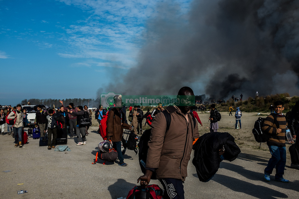 October 26, 2016 - Calais, France - Migrants leave the burning Calais Jungle, on October 26, 2016. Huge fires destroyed a mayor part of the refugee camp today. (Credit Image: © Markus Heine/NurPhoto via ZUMA Press)