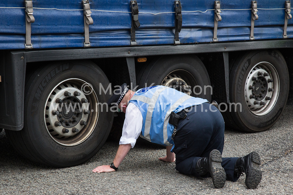 London, UK. 6 September, 2019. A Metropolitan Police officer monitors an activist locked beneath a truck making a delivery to ExCel London for DSEI, the world's largest arms fair. The road remained blocked for several hours. The fifth day of protests against the arms fair was themed as Stop The Arms Fair: Stop Climate Change in order to highlight links between the fossil fuel and arms industries.