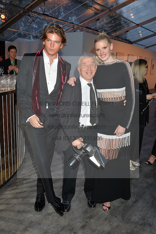 Left to right, JORDAN BARRY, JAMES PELTEKIAN and LARA STONE at British Vogue's Centenary Gala Dinner in Kensington Gardens, London on 23rd May 2016.