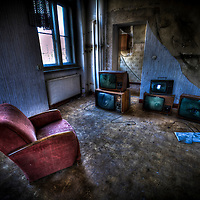 Disused room in large house with comfortable armchair and television sets