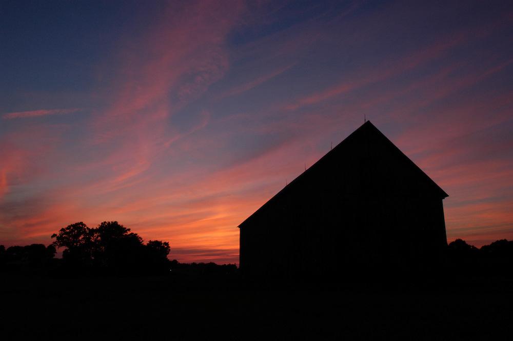 Sunset sky behind a barn