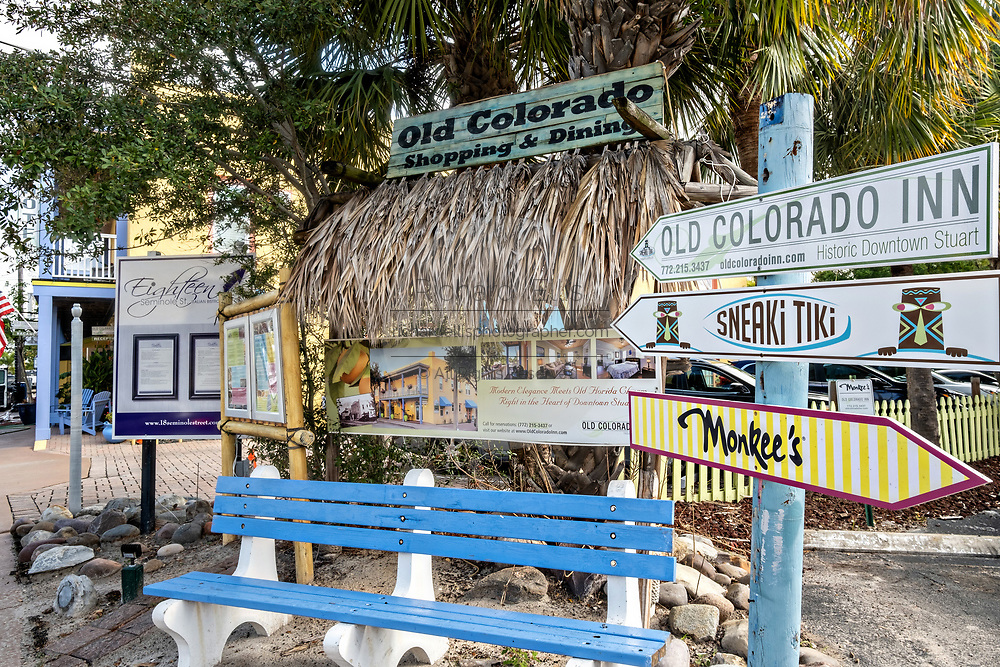 Park bench and signs in the historic downtown of Stuart, Florida. The tiny hamlet was founded in 1870 and was voted the Happiest Seaside Town in America by Coastal Living.