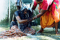 TAMIL NADU, MARCH 1994.A young woman succumbs and gets to the ground. The father keeps throwing buckets of 'holy water' over her body. Locals believe that her body is possessed by evil spirits and that faith is said to be the only remedy.