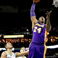 Dec 5, 2012; New Orleans, LA, USA; Los Angeles Lakers shooting guard Kobe Bryant (24) goes up for a dunk over New Orleans Hornets point guard Greivis Vasquez (21) and power forward Jason Smith (14) during the second quarter of a game at the New Orleans Arena.  The Lakers defeated the Hornets 103-87.  Mandatory Credit: Derick E. Hingle-USA TODAY Sports