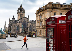 Edinburgh, Scotland, UK. 18 April 2020. Views of empty streets and members of the public outside on another Saturday during the coronavirus lockdown in Edinburgh. Man running on a deserted Royal Mile. Iain Masterton/Alamy Live News