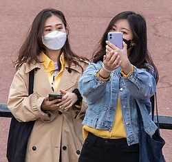 © Licensed to London News Pictures. 11/03/2020. London, UK. Two young women in masks do a selfie during the Changing of the Guards at Buckingham Palace as Health Minister, Nadine Dorries goes in to self-isolation after catching Covid19. Yesterday British Airways cancelled all flights to and from Italy as fears over the Coronavirus disease continues. Photo credit: Alex Lentati/LNP