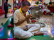 "22 AUGUST 2017 - BANGKOK, THAILAND: A man prays during a ceremony on the first day of Hungry Ghost Month at the Poh Teck Tung Shrine in Bangkok's Chinatown. The seventh lunar month (August - September) is when many Chinese believe Hell's gate will open to allow spirits to roam freely in the human world. Many households and temples hold prayer ceremonies throughout the month-long Hungry Ghost Festival (Phor Thor) to appease the spirits. During the festival, believers will also worship the Tai Su Yeah (King of Hades) in the form of paper effigies which will be ""sent back"" to hell after the effigies are burnt.      PHOTO BY JACK KURTZ"