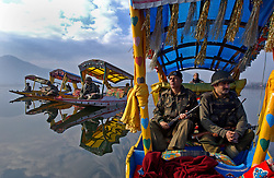 Indian Border Security Force Officers patrol the picturesque Dal Lake in the summer capital of  Srinagar in the Indian held state of Kashmir.  Once a tourist hotspot, the only  visitors to this magnificent landscape these days are Indian soldiers. (Ami Vitale)
