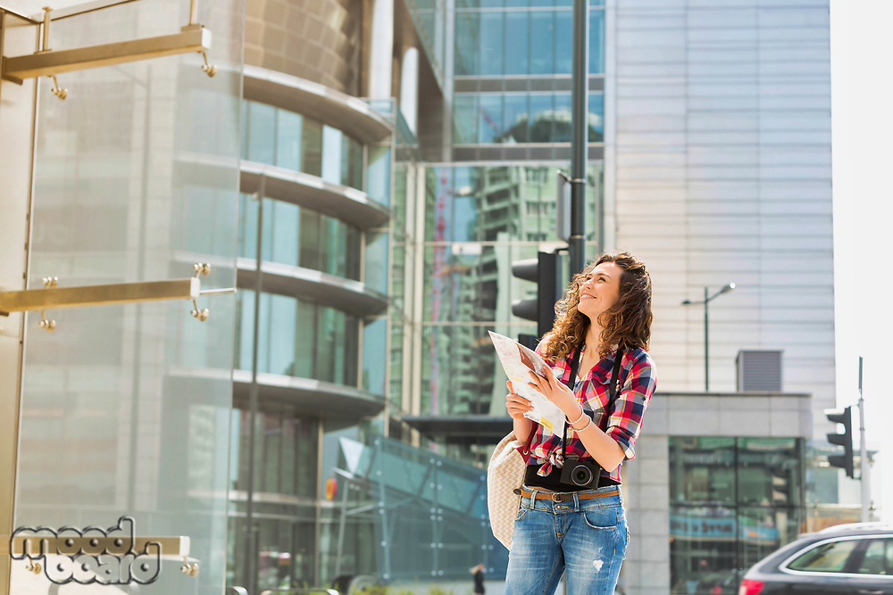 Portrait of young attractive woman looking on the map in the city