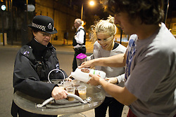 © Licensed to London News Pictures. 07/08/2011. London, UK. As looters and rioters smashed up shops, looted and fought with police in Camden Town, Philippa Morgan-Walker, 25 and her husband, Jonny Walker, 31, made tea for the police who were protecting their street. Some of the officers had been on duty for more than 30 hours. Photo credit : Joel Goodman/LNP