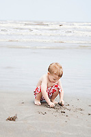 Boy crouching and playing with sand at water's edge