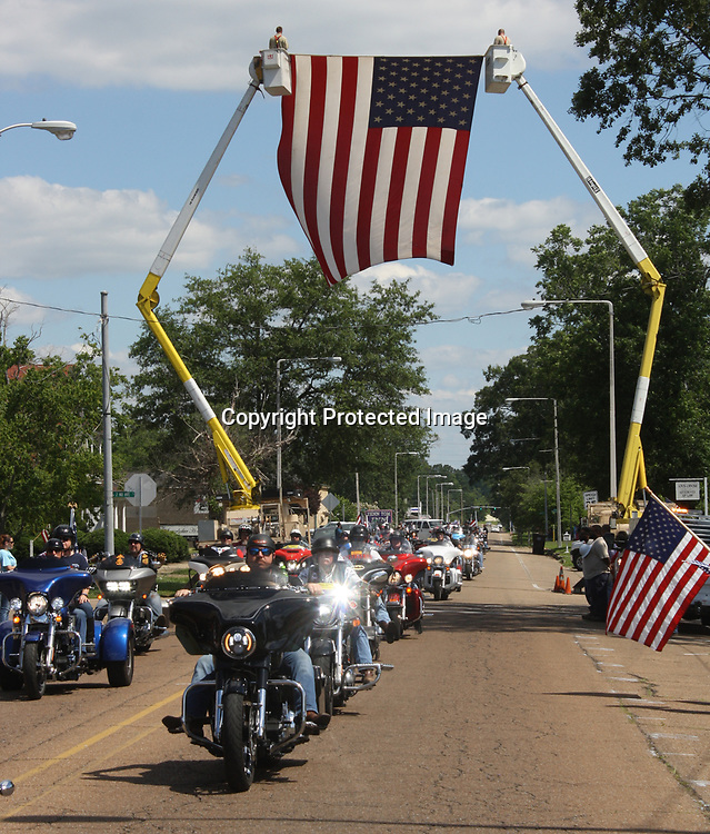 EMILY TUBB/BUY AT PHOTOS.MONROECOUNTYJOURNAL.COM<br /> Members of the Patriot Guard drive underneath an American flag being held by Amory Electric Department linemen at the intersection of Main Street and Second Avenue.