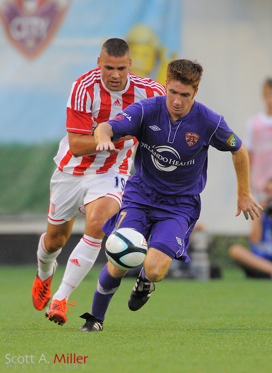 Stoke City Potters forward Jonathan Walters (19) and Orlando City Lions midfielder James O'Connor (17) chase down the ball during their match at the Florida Citrus Bowl on July 28, 2012 in Orlando, Florida. Stoke won the game 1-0...Scott A. Miller/ACTION IMAGES.