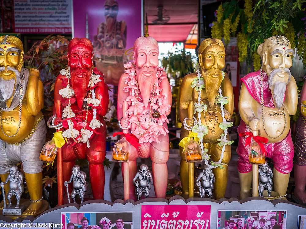 "28 FEBRUARY 2013 - BANGKOK, THAILAND: Statues of Chuchok in the Chuchok shrine. The Chuchok Shrine is in suburban Bangkok. More than 100 people a week come to the shrine to pray for good fortune or good health. People whose prayers are answered return to the shrine with ""coyote dancers"" to make merit and thank Chuchok. Coyote dancing is a Thai phenomenon created after the US movie ""Coyote Ugly"" where attractive young women dance in a sexually suggestive way, usually for pay. They're common at bars and festivals. Coyote dancers are typically better paid than other Thai women in the hospitality industry and usually are not allowed to date or see customers are off the dance floor. Coyote dancers perform at the Chuchok shrine because according to Buddhist literature Chuchok was a relatively repulsive old hermit and Brahmin priest who was cared for by a young woman after he made her family's wishes come true.   PHOTO BY JACK KURTZ"