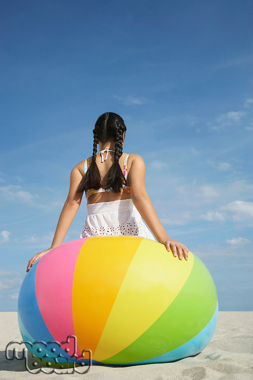 Teenage girl (16-17) sitting on large beach ball back view