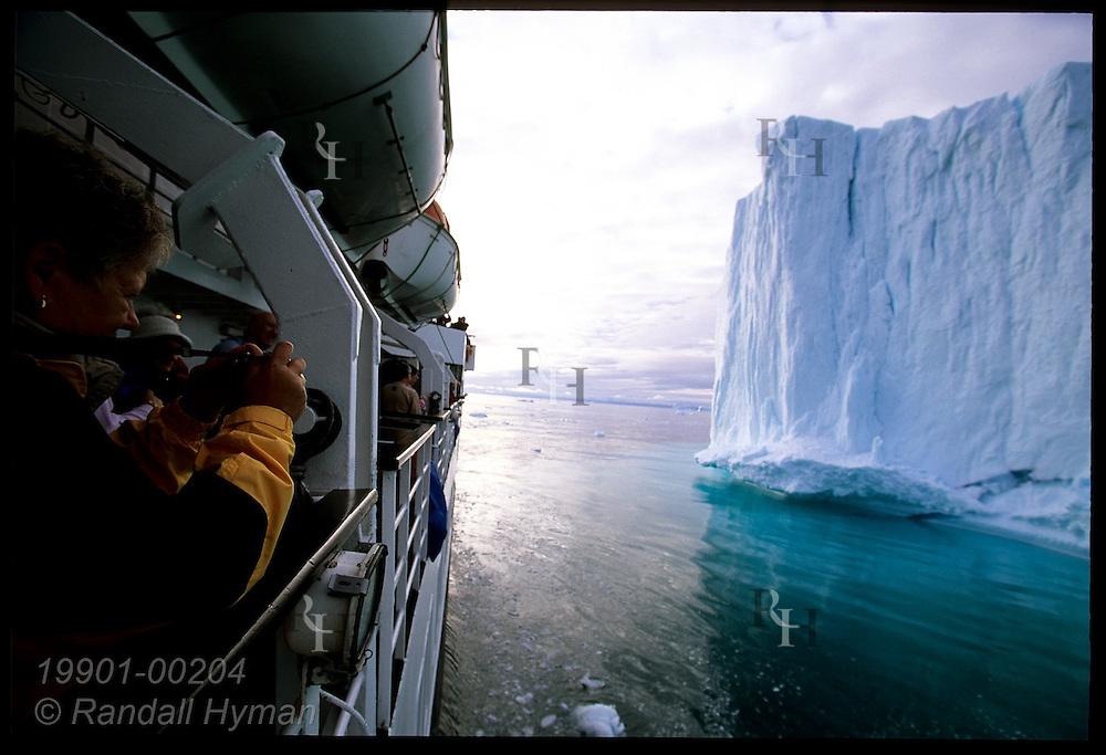 Passengers aboard the Clipper Adventurer cruise ship admire towering Disko Bay iceberg from upper deck; Ilulissat, Greenland