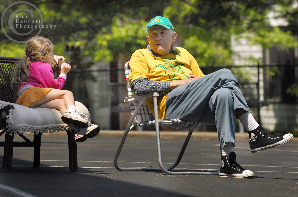 "Kevin ""The Commissioner"" Ettinger  sits with his granddaughter Cheyenne Ettinger, 5, during a game of stickball..---.The Ethical Stickball League has been operating since 1970, meeting every Sunday in the parking lot behind Hastings High School from 10:30AM to 1PM.  The players are men now mostly in their 70s - carrying nicknames like ""The Wise One"", ""Hit Man"" and ""Plays Hurt"" - who have an affiliation with the school, either as former teachers, students or neighbors. As their slogan suggests, all it takes for a few hours of ""Aestas Aeterna"" (Eternal Summer) is an outside temperature above 45 degrees and 8 willing souls...CREDIT: Rob Bennett for The NY Times"