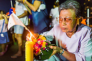 "17 NOVEMBER 2013 - BANGKOK, THAILAND:  A woman lights the candle on her krathong before floating it in the Chao Phraya River near Wat Yannawa in Bangkok. Loy Krathong (also written as Loi Krathong) is celebrated annually throughout Thailand and certain parts of Laos and Burma (in Shan State). The name could be translated ""Floating Crown"" or ""Floating Decoration"" and comes from the tradition of making buoyant decorations which are then floated on a river. Loi Krathong takes place on the evening of the full moon of the 12th month in the traditional and they do this all evening on the 12th month Thai lunar calendar. In the western calendar this usually falls in November. The candle venerates the Buddha with light, while the krathong's floating symbolizes letting go of all one's hatred, anger, and defilements      PHOTO BY JACK KURTZ"