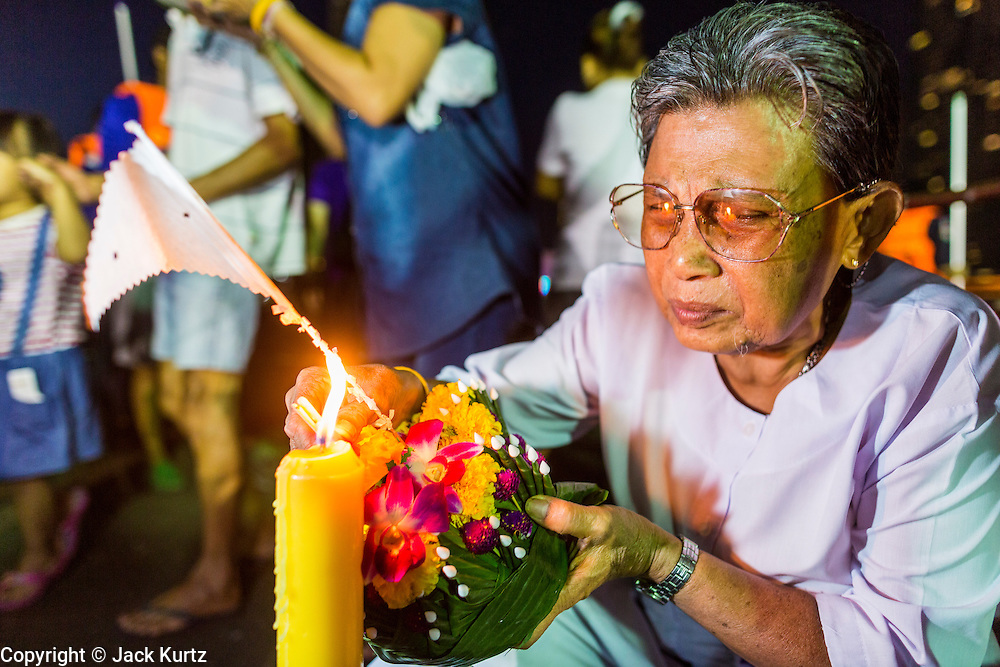 """17 NOVEMBER 2013 - BANGKOK, THAILAND:  A woman lights the candle on her krathong before floating it in the Chao Phraya River near Wat Yannawa in Bangkok. Loy Krathong (also written as Loi Krathong) is celebrated annually throughout Thailand and certain parts of Laos and Burma (in Shan State). The name could be translated """"Floating Crown"""" or """"Floating Decoration"""" and comes from the tradition of making buoyant decorations which are then floated on a river. Loi Krathong takes place on the evening of the full moon of the 12th month in the traditional and they do this all evening on the 12th month Thai lunar calendar. In the western calendar this usually falls in November. The candle venerates the Buddha with light, while the krathong's floating symbolizes letting go of all one's hatred, anger, and defilements      PHOTO BY JACK KURTZ"""
