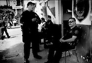 Confident swagger: Tijuana policemen sit outside of station in the middle of the Coahuila red light district, where men are frequently arrested, Zona Norte, Tijuana, Mexico.