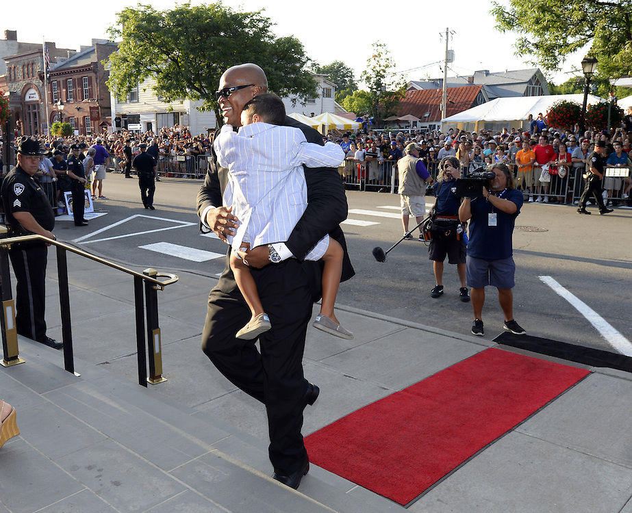 COOPERSTOWN, NY - JULY 26:  2014 Hall of Fame inductee Frank Thomas and his son Frankie III walk up the red carpet during the annual Parade of Legends down Main Street in Cooperstown, New York on July 26, 2014.