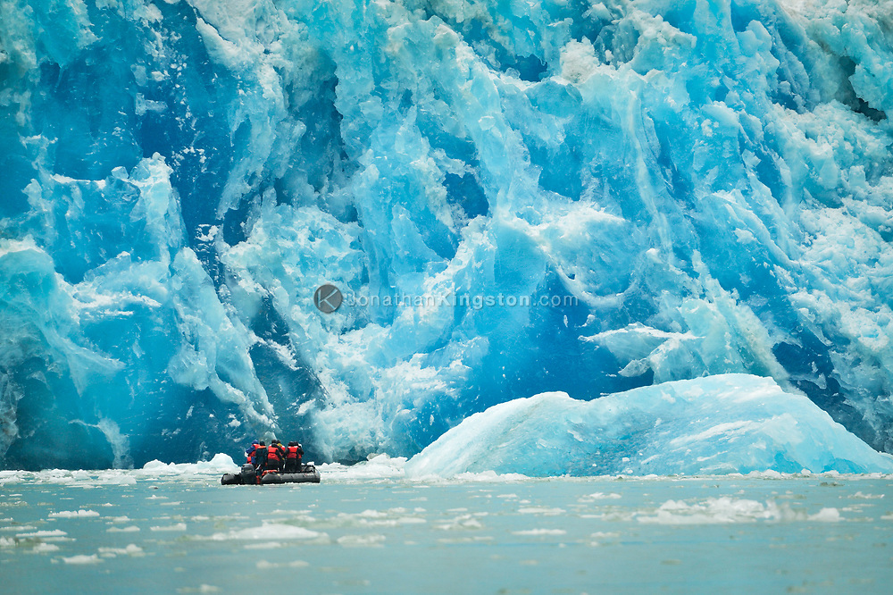 A small inflatable boat with tourists on it is dwarfed by the massive blue face of the Dawes glacier in Tracy Arm fjord near Juneau, Alaska.