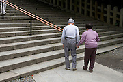 elderly Japanese couple walking towards stairs while holding hands