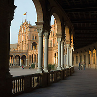 Three people walking in the colonnade of the 1929 Exposition Building, Plaza de España, Sevilla, Andalucia, Spain.