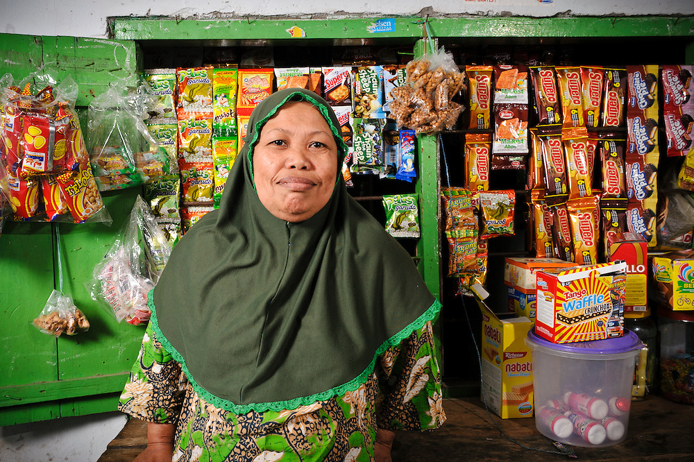 Ibu Bunga outside her kiosk at the Jongaya leprosy settlement, Makassar, Sulawesi, Indonesia. Ibu Bunga, 33, discovered she had leprosy when she was 9 and moved to the Jongaya leprosy settlement within a year.  She is originally from Makassar.  She lives with her husband and grandmother and now runs a small kiosk from her home.  Ibu Bunga started the kiosk using money borrowed from Permata as part of a credit scheme set up to support small businesses in the settlement.