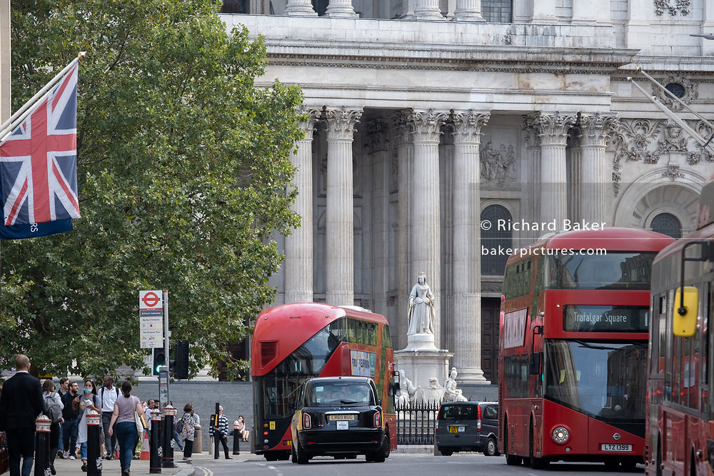 Cars and buses at the top of Ludagte Hill with the columns of St. Paul's Cathedral and the statue of Queen Victoria, on 16th September 2020, in London, England.