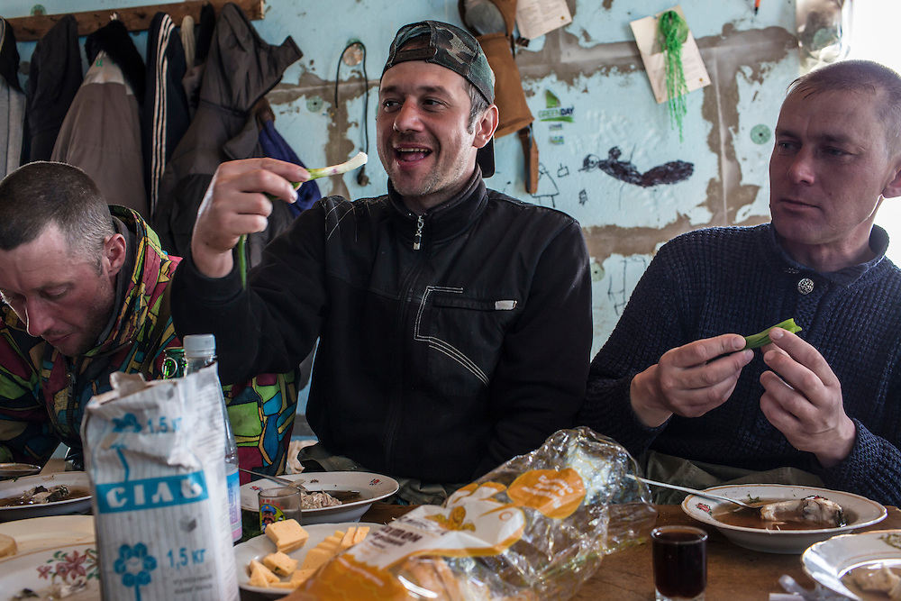 Fishermen eat ukha, a traditional Russian fish soup, and fresh greens after a morning of work on Saturday, April 11, 2015 in Siedove, Ukraine.