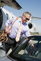 Senior businessman getting of airplane and getting in car.