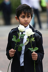 © Licensed to London News Pictures. 15/07/2016. Batley, UK. A boy holds flowers as she waits for Jo Cox's funeral cortege to pass through her hometown of Batley, West Yorkshire. The Labour MP was stabbed and shot in the street as she left her constituency surgery last month. Thomas Mair was arrested in connection with the murder and is set to face trial this year.  Photo credit : Ian Hinchliffe/LNP