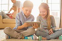 Happy siblings using digital tablet on floor with parents in background