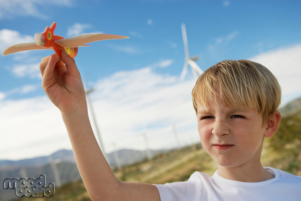 Boy (7-9) playing with toy glider at wind farm