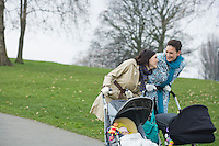 Two mothers pushing strollers in park