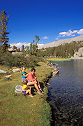 Mother and kids (ages 6 & 3) relaxing on the shore of Long Lake, John Muir Wilderness, Sierra Nevada Mountains, California