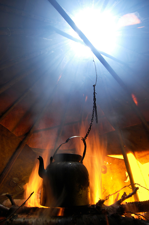Coffee Pot boiling in a traditional Sami tent, a Goahti, or Kåta, on a Reindeer sledding safari ecotourism, Sami tour outfitter Per-Nils Päiviö, Nature's Best, Övre Soppero, Lapland, Norrbotten, Sweden.