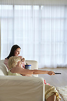 Two women sitting on sofa watching television