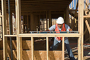 Construction worker using spirit level on construction site