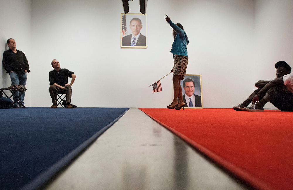 "Wynona Parks of Los Angles (center) watches election coverage in a space titled ""Your Land / My Land"" by artist Jonathan Horowitz during Election Night at the Hammer Museum on November 6, 2012 in Los Angeles. ""Your Land / My Land"" installation divides the room in half by using red and blue carpets along with two televisions playing Fox News (red) and MSNBC (blue). The separation brings attention to the two party system in US politics today. (Photo by Michael Yanow)"