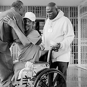 """Hospice volunteer Nolan James, left, and hospice patient, Kenny Mingo, right, lift Albert """"Tut"""" Soublet from his wheelchair so he can go through a security checkpoint. Soublet is a palliative care hospice patient and he continues to live in the main prison. Volunteers visit palliative patients daily and help them live in the main population for as long as possible."""