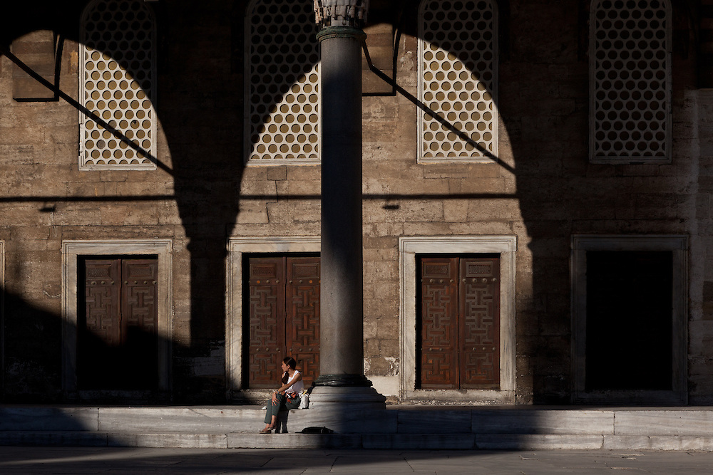 Woman in a sunlit arch, Sultan Ahmed (Blue) Mosque, Istanbul, Turkey.
